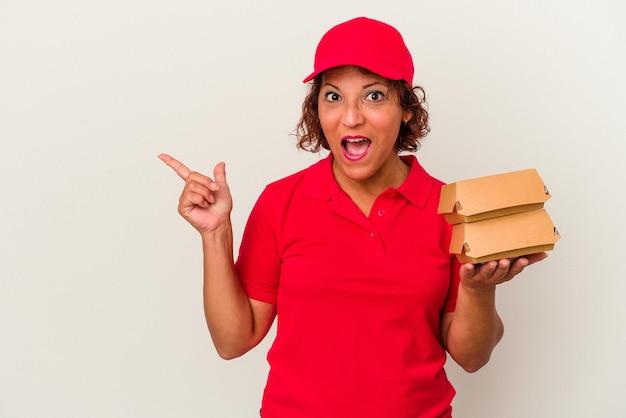 Kobieta w średnim wieku dostarczająca hamburgery na białym tle, wskazując na bok