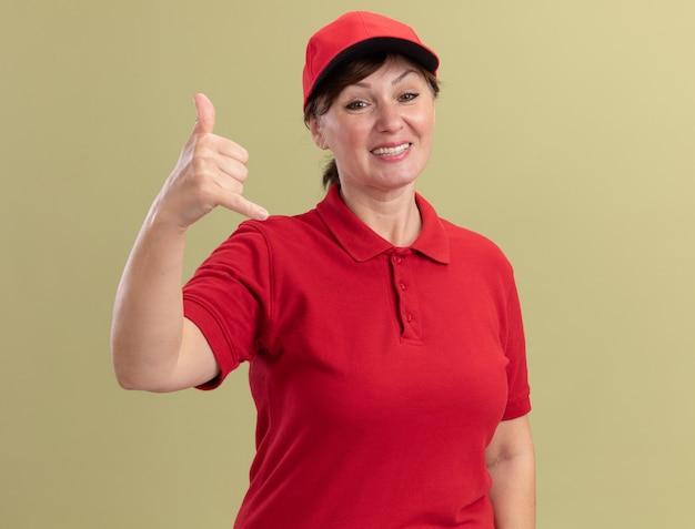 Kobieta w średnim wieku dostawy w czerwonym mundurze i czapce patrząc na przód uśmiechając się radośnie, wykonując wezwanie do mnie gest stojąc na zielonej ścianie