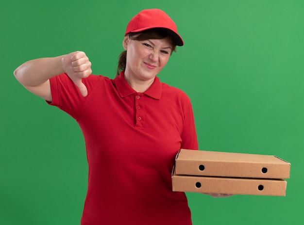 Kobieta w średnim wieku dostawy w czerwonym mundurze i czapce trzyma pudełka po pizzy patrząc na przód jest zdezorientowana pokazując kciuki w dół stojąc nad zieloną ścianą