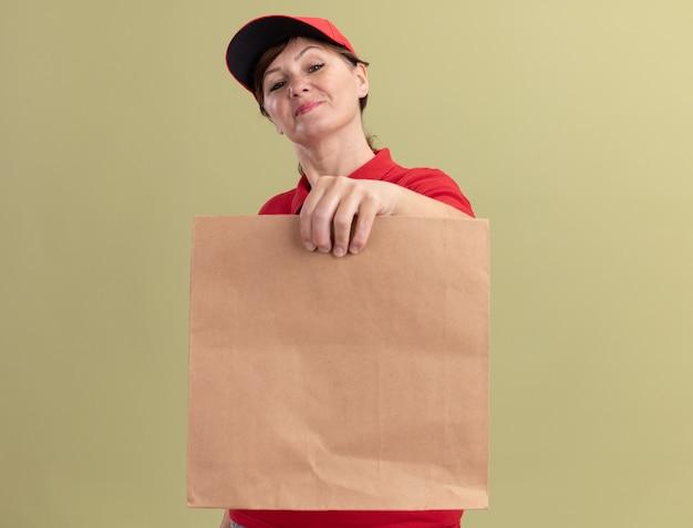 Kobieta w średnim wieku dostawy w czerwonym mundurze i czapce, trzymając papierowy pakiet patrząc z przodu uśmiechnięta pewnie stojąca nad zieloną ścianą