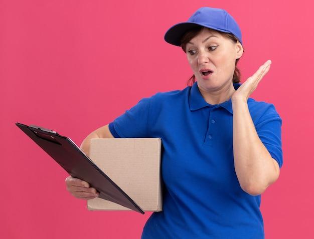 Kobieta w średnim wieku dostawy w niebieskim mundurze i czapce, trzymając karton patrząc na schowek jest zdezorientowany stojąc nad różową ścianą