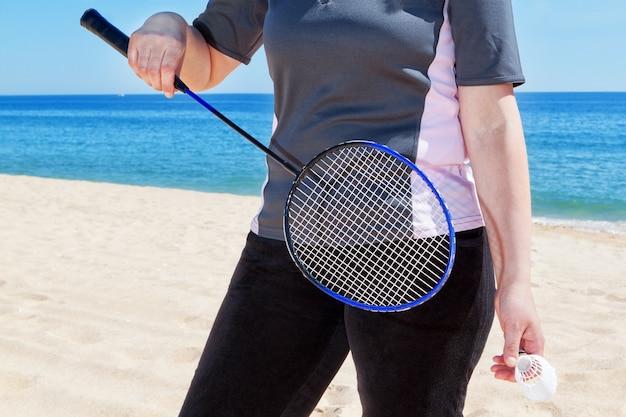 Kobieta w średnim wieku, grając w badmintona na plaży. lato.