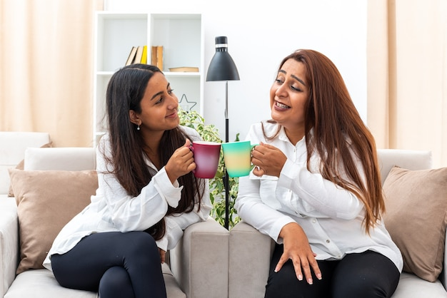 Kobieta w średnim wieku i jej młoda córka w białych koszulach i czarnych spodniach siedzących na krzesłach z kubkami gorącej herbaty szczęśliwe i pozytywne spędzanie czasu razem w jasnym salonie