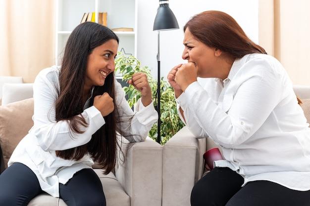 Kobieta w średnim wieku i młoda dziewczyna w białych koszulach i czarnych spodniach kłócą się zaciskając pięści siedząc na krzesłach w jasnym salonie