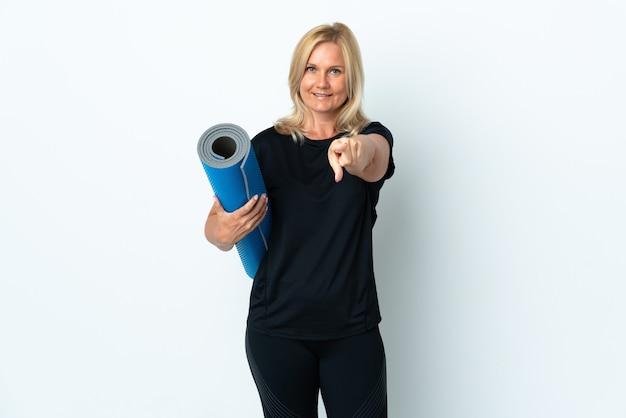 Kobieta w średnim wieku idąca na zajęcia jogi, trzymając matę na białej ścianie wskazuje palcem na ciebie z pewnym siebie wyrazem twarzy