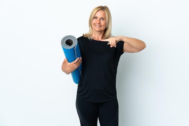 Kobieta w średnim wieku idzie na zajęcia jogi, trzymając matę na białej ścianie i wskazując ją