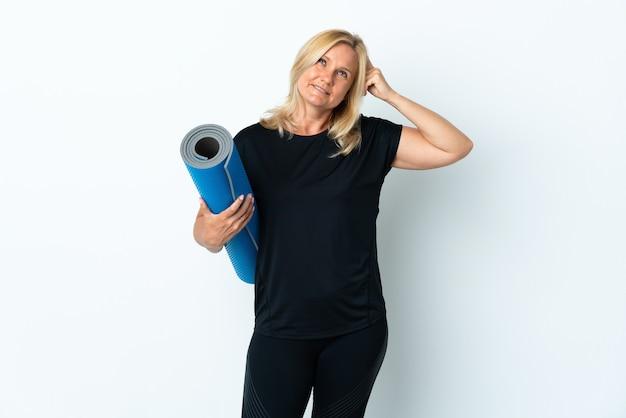 Kobieta w średnim wieku idzie na zajęcia jogi, trzymając matę na białej ścianie, mając wątpliwości iz niejasnym wyrazem twarzy