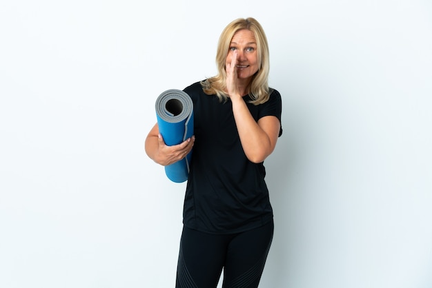 Kobieta w średnim wieku idzie na zajęcia jogi, trzymając matę na białej ścianie szepcząc coś