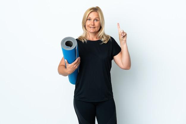 Kobieta w średnim wieku idzie na zajęcia jogi, trzymając matę na białej ścianie, wskazując na świetny pomysł