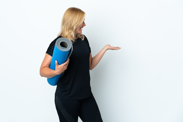 Kobieta w średnim wieku idzie na zajęcia jogi, trzymając matę na białej ścianie z wyrazem twarzy zaskoczenia