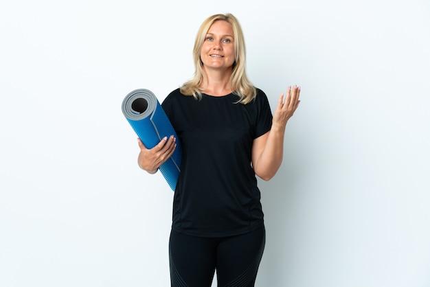 Kobieta w średnim wieku idzie na zajęcia jogi, trzymając matę na białej ścianie, zapraszając do ręki. cieszę się, że przyszedłeś