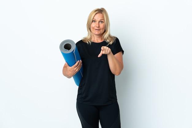 Kobieta w średnim wieku idzie na zajęcia jogi trzymając matę na białej ścianie zaskoczony i wskazując przód