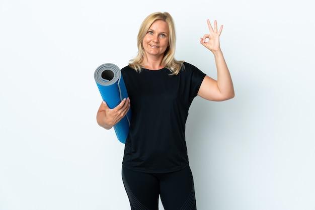 Kobieta w średnim wieku idzie na zajęcia jogi, trzymając matę na białym tle na białej ścianie, pokazując znak ok palcami