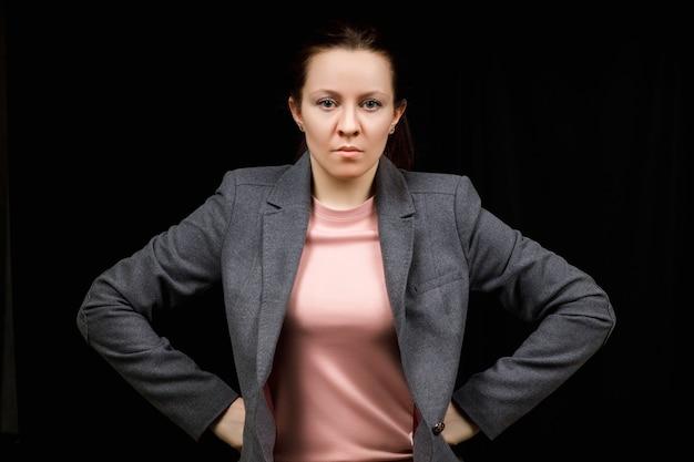 Kobieta w średnim wieku jest zła. dziewczyna nosi dorywczo słodsze na czarno. zła kobieta, ręce po bokach.