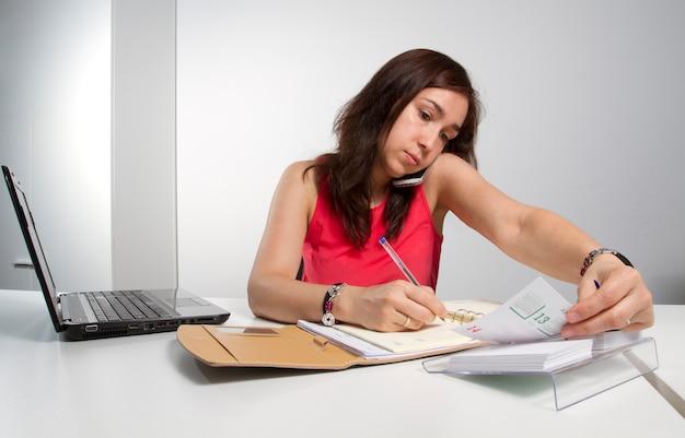 Kobieta w średnim wieku konsultuje swój program i mówi przez telefon