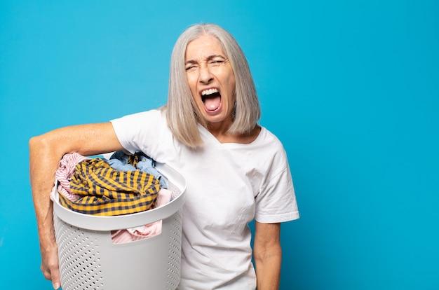 """Kobieta w średnim wieku krzycząca agresywnie, wyglądająca na bardzo rozgniewaną, sfrustrowaną, oburzoną lub zirytowaną, krzyczącą """"nie"""""""