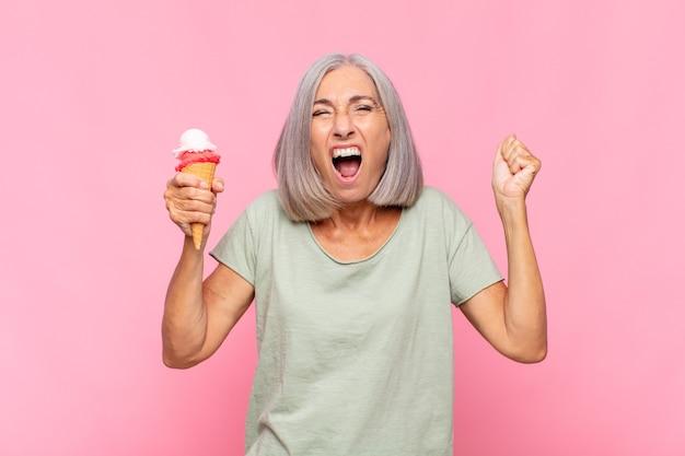 Kobieta w średnim wieku krzycząca agresywnie z gniewnym wyrazem twarzy lub z zaciśniętymi pięściami świętująca sukces przy lodach