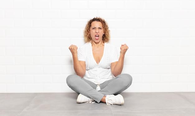 Kobieta w średnim wieku krzycząca agresywnie z gniewnym wyrazem twarzy lub z zaciśniętymi pięściami świętująca sukces