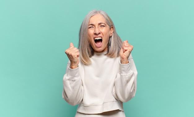 Kobieta w średnim wieku krzycząca agresywnie ze zirytowanym, sfrustrowanym, gniewnym spojrzeniem i zaciśniętymi pięściami, czując się wściekła