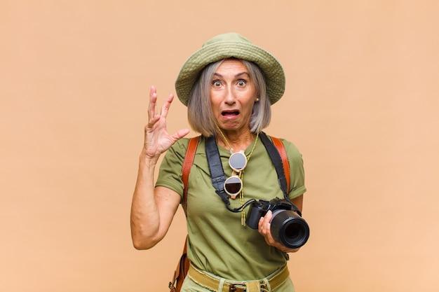 Kobieta w średnim wieku krzycząca z podniesionymi rękami, wściekła, sfrustrowana, zestresowana i zdenerwowana