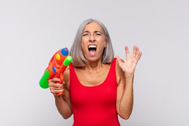 Kobieta w średnim wieku krzycząca z rękami do góry, wściekła, sfrustrowana, zestresowana i zdenerwowana pistoletem na wodę