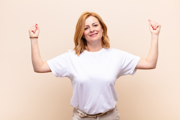 Kobieta w średnim wieku krzyczy triumfalnie, wyglądając jak podekscytowany, szczęśliwy i zaskoczony zwycięzca, świętujący