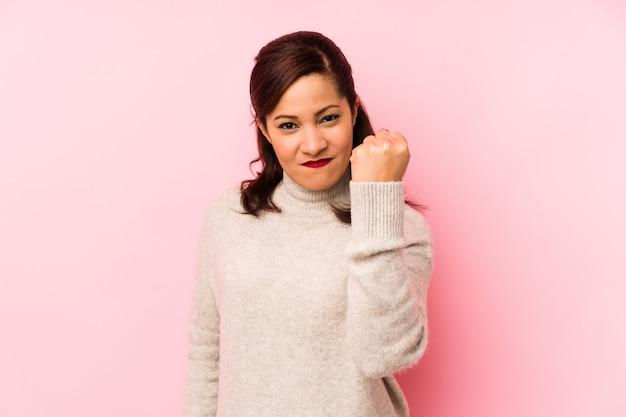 Kobieta w średnim wieku łacińskiej samodzielnie na różowo, pokazując pięść, agresywny wyraz twarzy.
