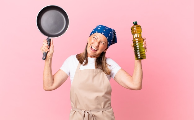 Kobieta w średnim wieku, ładna szefowa kuchni, trzymająca patelnię i butelkę oliwy z oliwek