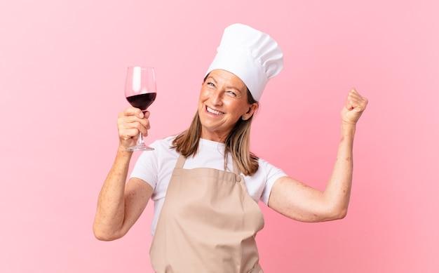 Kobieta w średnim wieku, ładna szefowa kuchni z kieliszkiem wina