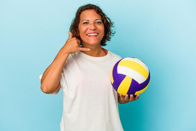 Kobieta w średnim wieku latin gra w siatkówkę na białym tle na niebieskim tle pokazując gest połączenia z telefonu komórkowego palcami.