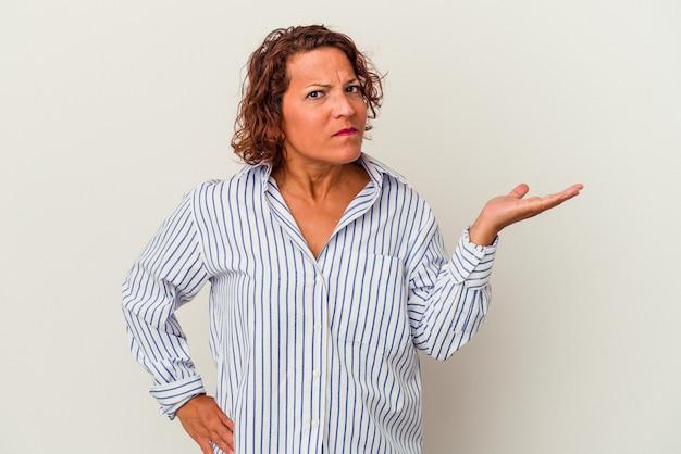 Kobieta w średnim wieku latin na białym tle wątpiąc i wzruszając ramionami w geście przesłuchania.