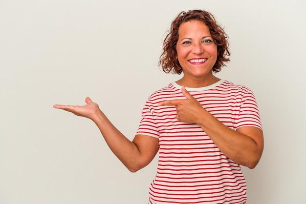 Kobieta w średnim wieku latin samodzielnie na białym tle podekscytowany, trzymając miejsce na kopię na dłoni.