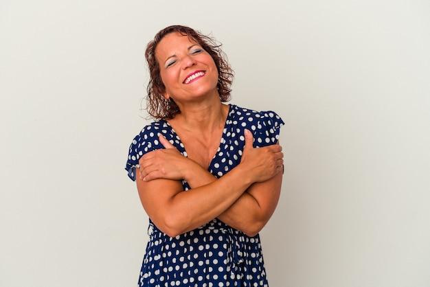 Kobieta w średnim wieku latynoska na białym tle przytula się, uśmiechając się beztrosko i szczęśliwie.