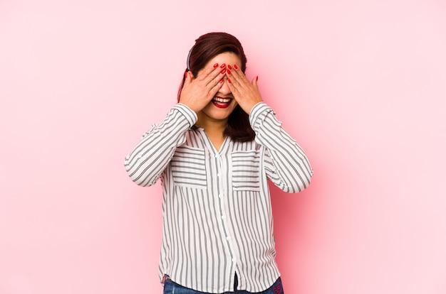 Kobieta w średnim wieku, latynoska na różowo, zakrywa oczy dłońmi, uśmiecha się szeroko, czekając na niespodziankę.