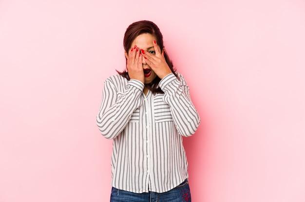Kobieta w średnim wieku, latynoska na różowym tle, mruga przez palce przestraszone i zdenerwowane.