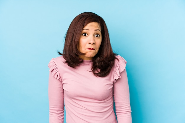 Kobieta w średnim wieku, latynoska, wzrusza ramionami i wprawia w osłupienie otwarte oczy.