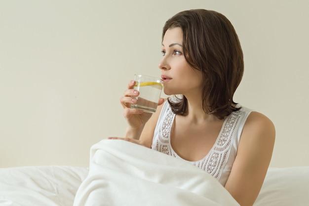 Kobieta w średnim wieku lubi wodę z cytryną siedzącą w łóżku