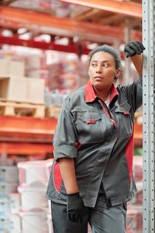 Kobieta w średnim wieku, mieszana rasa, pracownica dużego współczesnego magazynu w rękawiczkach i odzieży roboczej, patrząca na bok podczas odpoczynku przy stojaku
