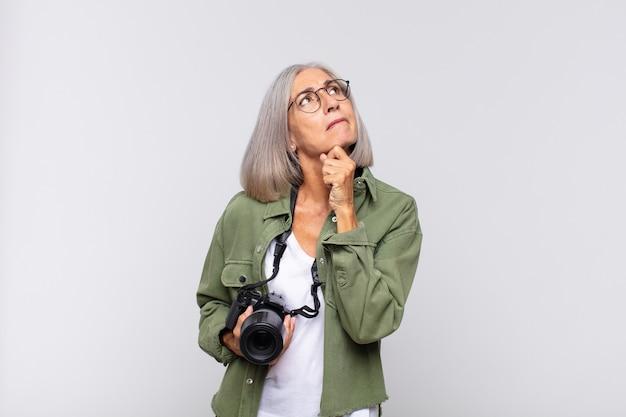 Kobieta w średnim wieku myśli, czuje się niepewna i zagubiona, ma różne opcje, zastanawia się, którą decyzję podjąć. koncepcja fotografa