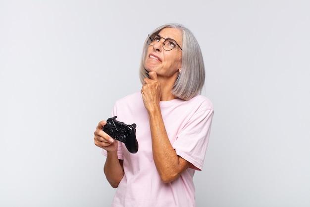 Kobieta w średnim wieku myśli, czuje się niepewna i zagubiona, ma różne opcje, zastanawia się, którą decyzję podjąć. koncepcja konsoli do gry