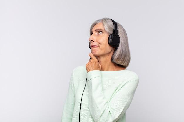 Kobieta w średnim wieku myśli, czuje się niepewna i zagubiona, ma różne opcje, zastanawia się, którą decyzję podjąć. koncepcja muzyki