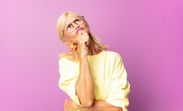 Kobieta w średnim wieku myśli, czuje się niepewna i zagubiona, ma różne opcje, zastanawia się, którą decyzję podjąć