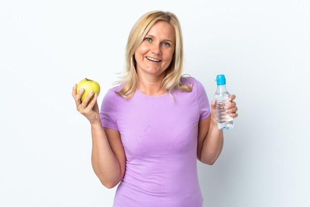 Kobieta w średnim wieku na białym tle na białej ścianie z jabłkiem i butelką wody