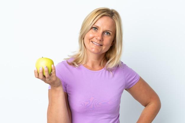 Kobieta w średnim wieku na białym tle na białej ścianie z jabłkiem i szczęśliwa
