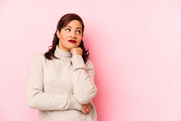 Kobieta w średnim wieku, na białym tle na różowo, która czuje się smutna i zadumana, patrząc na miejsce.