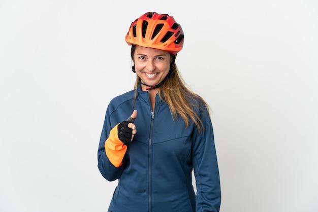 Kobieta w średnim wieku na rowerze na białym tle zaskoczona i wskazująca przód