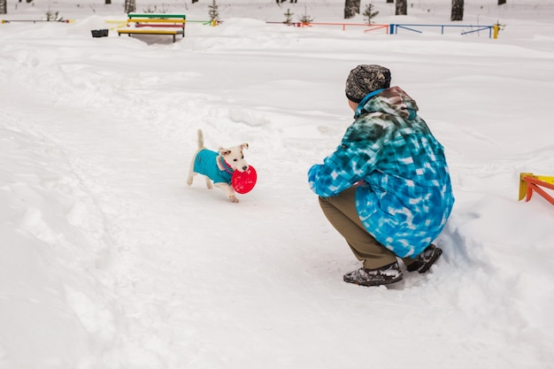 Kobieta w średnim wieku na zewnątrz z uroczym psem - jack russell terrier w sezonie zimowym