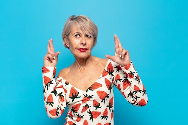 Kobieta w średnim wieku niespokojnie trzymająca palce z nadzieją na szczęście i zmartwionym spojrzeniem