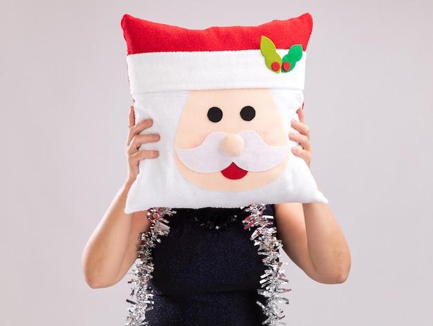 Kobieta w średnim wieku nosząca czapkę mikołaja i girlandę z blichtru wokół szyi, trzymająca poduszkę świętego mikołaja przed twarzą na białym tle