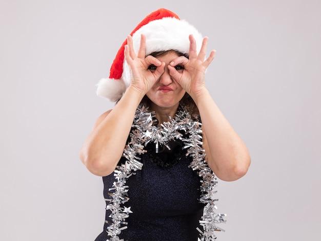 Kobieta w średnim wieku nosząca santa hat i girlandę blichtr wokół szyi patrząc na kamery robi gest spojrzenia za pomocą rąk jako lornetki na białym tle